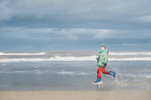 Denmark, Skagen, boy in winter clothes running on beach - MJF02013