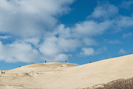 Denmark, North Jutland, people running in wandering dune at lighthouse Rubjerg Knude - MJF02043