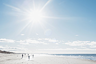Denmark, Hirtshals, people walking on beach in backlight - MJF02067