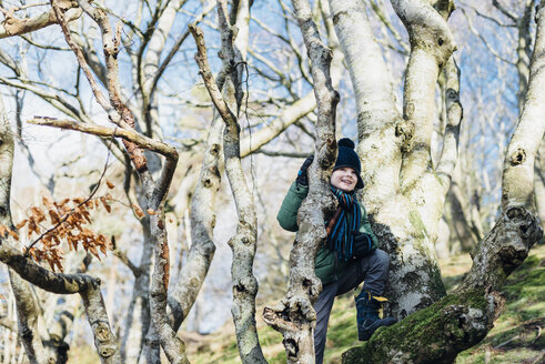 Boy climbing on a tree in winter clothes - MJF02070