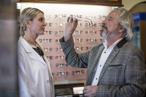 Optician helping customer to choose new spectacles - ZEF10404