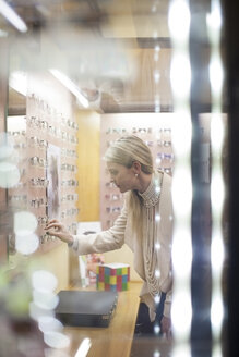 Blond woman selecting new glasses in opticians shop - ZEF10407