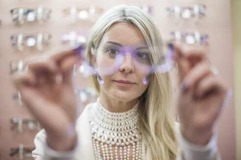 Blond woman selecting new glasses in opticians shop - ZEF10410