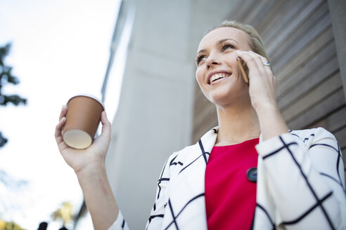 Smiling woman with takeaway coffee talking on cell phone - ZEF10485