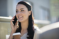 Smiling woman with takeaway coffee talking on cell phone - ZEF10494