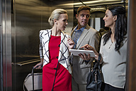 Business people in elevator with tablet talking - ZEF10503