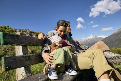 Family on a hiking trip resting on a bench - FSF00561