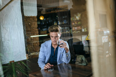 Young man sitting in a bar ooking at his cell phone - KIJF00841