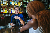 Waiter serving wine to a woman at the bar - KIJF00850
