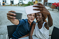 Young couple taking selfies at outdoor cafe - KIJF00859
