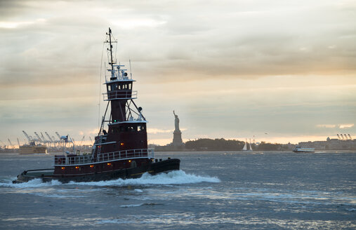 USA, New York City, tugboat on Upper New York Bay with Statue of Liberty in background - STCF00261