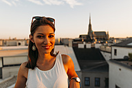 Austria, Vienna, portrait of smiling young woman on rooftop at sunset with Stephansdom in the background - AIF00373
