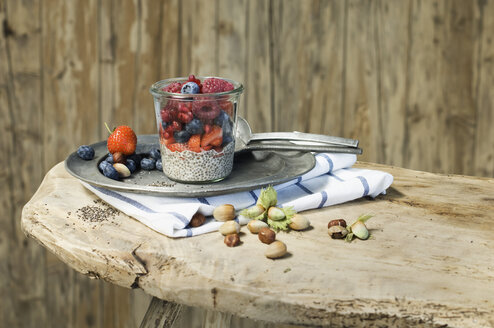 Glasses of chia pudding with different berries, pomegranate seeds and hazelnuts - ASF06024
