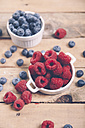 Bowls of raspberries and blueberries on wood - RTBF00414