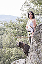 Portrait of smiling archeress with her dog in nature - ABZF01318