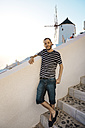 Greece, Santorini, Oia, man leaning on a wall - GEMF01091