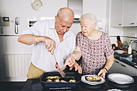 Senior couple serving stuffed eggplants in the kitchen - GEMF01115
