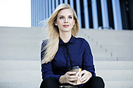 Portrait of blond businesswoman sitting on stairs with coffee to go - GDF01128