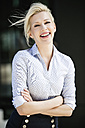 Portrait of laughing blond businesswoman with arms crossed - GDF01140