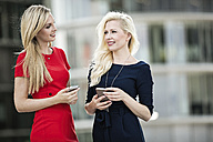Two fashionable businesswomen with smartphones - GDF01143