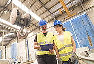 Woman showing clipboard to colleague in factory hall - JASF01153
