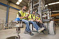 Workers having lunch on the shovel of a giant forklift - JASF01174
