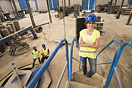 Portrait of smiling woman in factory hall with coworkers in background - JASF01180