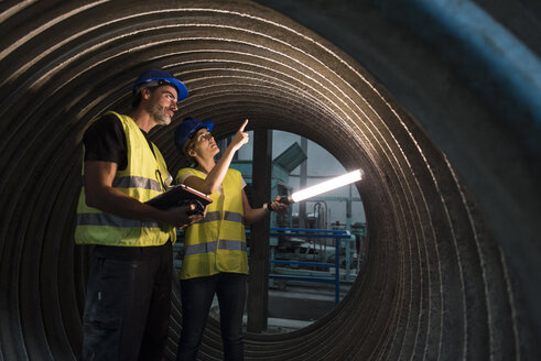 Man and woman examining giant construction tube - JASF01183