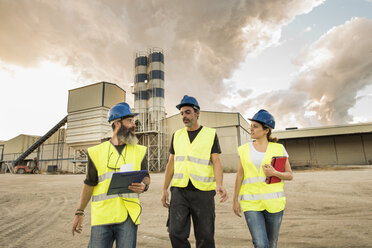 Three people in safety vests on industrial site - JASF01195