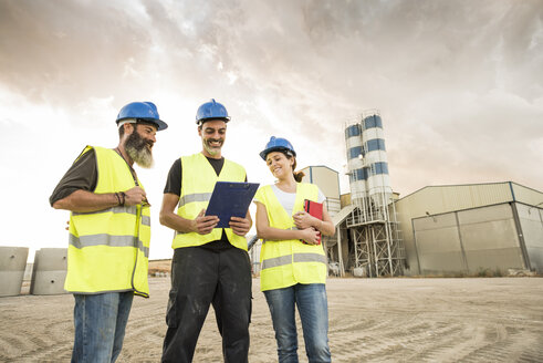 Three people in safety vests on industrial site - JASF01198