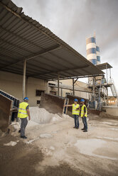 Three people in safety vests on industrial site looking at looking sand deposit - JASF01201