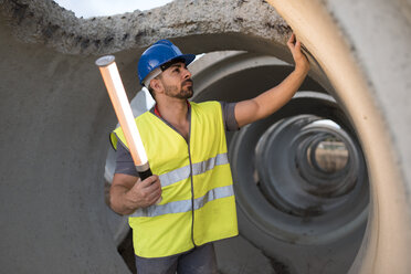 Construction worker examining concrete pipes - JASF01204