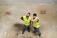 Two workers standing and looking up - JASF01216