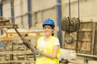Smiling woman operating control in factory - JASF01219