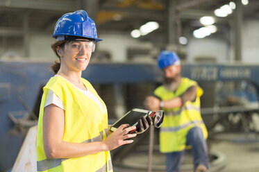 Portrait of smiling woman with tablet in factory hall - JASF01222