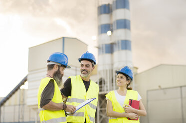 Three people in safety vests on industrial site - JASF01231