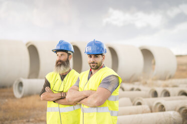Two workers posing outdoors near to concrete pipes - JASF01234