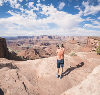 USA, Utah, Young man standing on Dead Horse Point photographing Colorado River - EPF00156