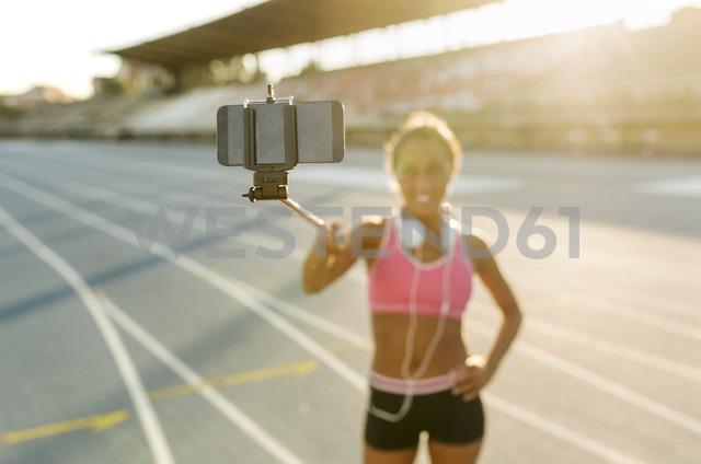 Female athlete taking selfies in stadium, holding selfie stick - MGOF02498
