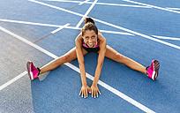 Female athlete stretching in stadium - MGOF02507