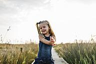 Happy little girl standing on boardwalk in nature - JRFF00866