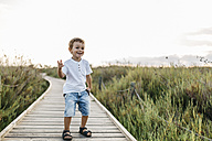 Happy little boy standing on boardwalk in nature - JRFF00869