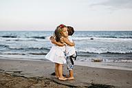 Little girl hugging little boy on the beach - JRFF00881