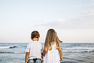 Back view of little boy and girl standing side by side in front of the sea - JRFF00884