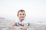 Portrait of happy little boy lying on the beach - JRFF00896