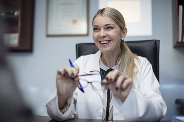 Female optometrist talking to patient, holding spectacles - ZEF10576