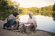 Senior couple lighting a campfire at a lake in the evening - ONF01044