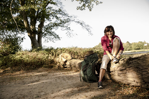 Senior woman with backpack resting on trunk - ONF01053