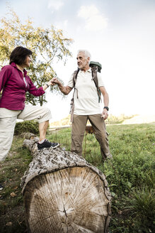 Senior couple on a hike crossing tree trunk - ONF01059