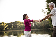 Happy senior couple hand in hand at a lake - ONF01071